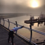 Back bending over the fog at the breakwater, Victoria BC